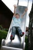 Boy on slide Stock Images