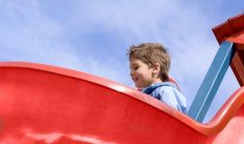 Boy on the slide. Happy boy on the sunlit slide against blue sky royalty free stock images