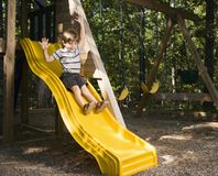 Boy on slide. Hispanic boy sliding down outdoor slide with arms raised above head royalty free stock photography