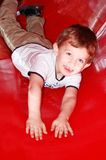 Boy in slide. Autistic happy little boy in a red slide stock image