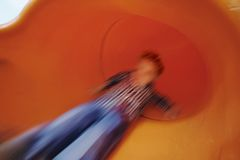 Boy on slide in motion stock photos