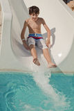 Boy on slide at waterpark Stock Photography