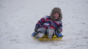 Boy slides down the mountain in the snow. Winter, leisure, sport, and people concept - happy teenage boy or young man sliding down on snow tube over mountain stock video