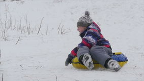 Boy slides down the mountain in the snow. Winter, leisure, sport, and people concept - happy teenage boy or young man sliding down on snow tube over mountain stock video footage