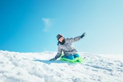 Boy slides down from the snow slope. Enjoying the winter sleddin. G time Royalty Free Stock Photography