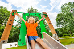 Boy slides on playground chute with hands up Stock Photography