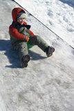 Boy sliding down. Young boy sliding down icy pathway on hillside in Winter Royalty Free Stock Images