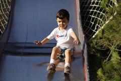 Boy sliding down outdoor slide Stock Photos