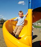 Boy sliding down a slide at the park Royalty Free Stock Images
