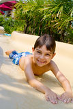 Boy Sliding Down Water Slide. Stock Photos