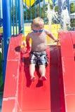 Boy sliding down a water slide Stock Photos