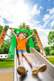 Boy sliding on metallic chute with hands up Stock Image