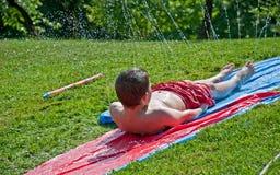 Boy Sliding on Plastic in Summer Sprinkler Stock Photo