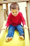 Boy sliding on playground Stock Images