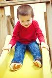 Boy sliding on playground Stock Images