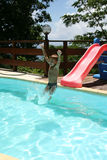 Boy sliding in the pool Royalty Free Stock Photography