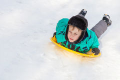 Boy sliding on snow saucer Royalty Free Stock Photography