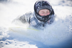 Boy sliding in the snow Royalty Free Stock Photography
