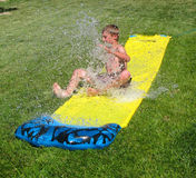 Boy Sliding Through Water. Young boy splashing water as he slides through on a hot summer day stock photography