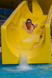 Fun in aquapark. Boy is sliding in yellow watr halfpipe in aquapark Stock Photo