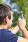 Boy with a slingshot aim to the tree Royalty Free Stock Images