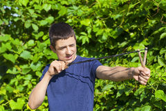 Boy with a slingshot near the bush Stock Photo