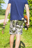 Boy with a slingshot and skateboard Royalty Free Stock Photo