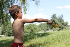 Boy with a slingshot standing outdoors. Boy in red shorts. Behind boy green trees Stock Photos