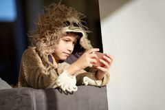 Boy in sloth pajamas playing mobile phone royalty free stock photography