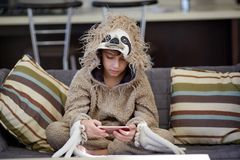 Boy in sloth pajamas playing mobile phone royalty free stock photos
