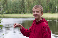 Boy with small fish. Smiling boy in red coat with small fish in his hand Stock Photography