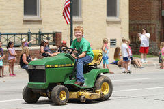 Boy on small tractor in a parade in small town America royalty free stock photography