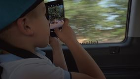 Kid in the car taking cell photos of city street. Boy with smart phone taking mobile photos of town through the window during car journey stock video footage