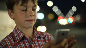Boy with a smartphone in hand on the background of night city lights. Boy with smartphone in hand on the background of night city lights stock footage