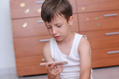 Boy with smartphone at home Stock Photography