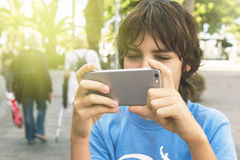 Boy with smartphone on street Stock Image