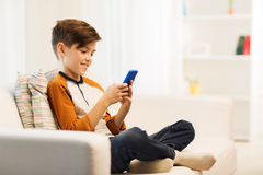 Boy with smartphone texting or playing at home Royalty Free Stock Photos