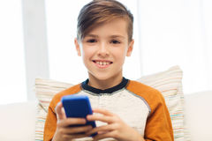 Boy with smartphone texting or playing at home Stock Photos