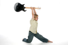 Boy smashing guitar. Young boy holding guitar over his head like he's going to smash it Stock Images