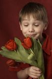 Boy smelling flowers Royalty Free Stock Photography