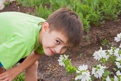 A boy smells flowers on a suburban Royalty Free Stock Photos