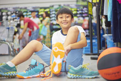 Boy smilding trying sports shoes in shopping mall Stock Photos