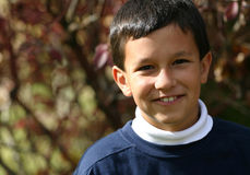 Boy Smiles. A young 9 year old Hispanic American boy smiling. Taken outside during the Fall season, red leaves behind, he wears a white turtleneck shirt and blue Royalty Free Stock Images
