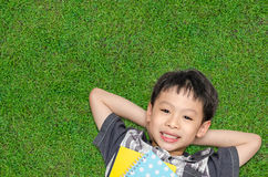Boy smiles on grass field. Top view of Asian boy smiles and lying on grass field Stock Photo