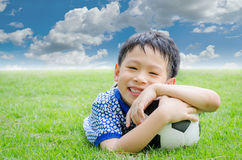 Boy smiles with his football on field Stock Image