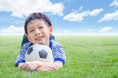 Boy smiles with his football on field Stock Photos