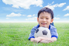 Boy smiles with his football on field Stock Photography