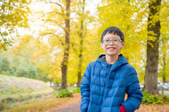Boy smiles with yellow leave in background Stock Photography