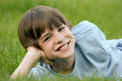 Boy Smiling. Young Boy Laying in the Grass Smiling Stock Image