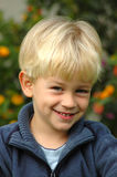 Boy smiling. A beautiful clever blond caucasian white boy child head portrait with happy ans smart smiling expression in his handsome face watching in the garden Stock Images
